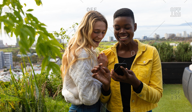 Front view of a Caucasian and an African American women hanging out on a roof terrace on a sunny day, using a smartphone and smiling