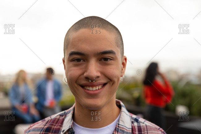 Portrait of a mixed race man hanging out on a roof terrace on a sunny day, looking at camera and smiling, with people talking in the background