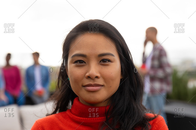 Portrait of an Asian woman hanging out on a roof terrace on a sunny day, looking at camera and smiling, with people talking in the background
