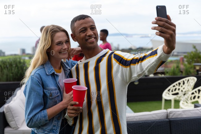 Front view of a Caucasian woman and an African American man hanging out on a roof terrace on a sunny day, taking a selfie and smiling