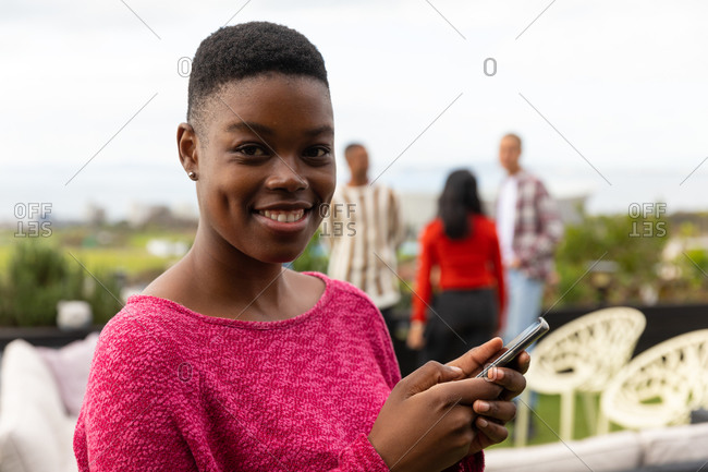Portrait of an African American woman hanging out on a roof terrace on a sunny day, looking at camera, smiling, holding a smartphone, with people talking in the background