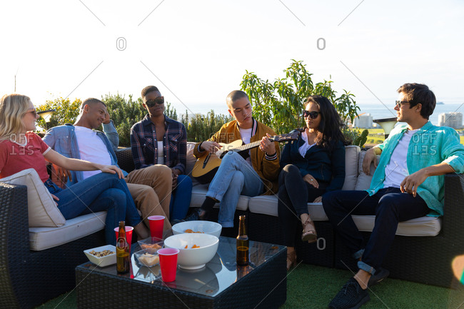Front view of a multi-ethnic group of friends hanging out on a roof terrace on a sunny day, one of them playing the guitar