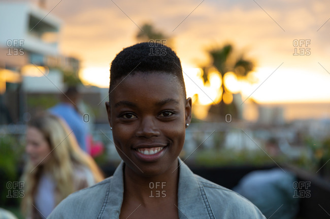 Portrait of an African American woman hanging out on a roof terrace with a sunset sky, looking at camera and smiling, with people talking in the background