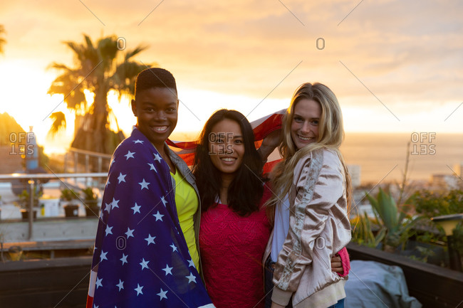 Portrait of a multi-ethnic group of friends hanging out on a roof terrace with a sunset sky, looking at camera and smiling, with an American flag draped around their shoulders