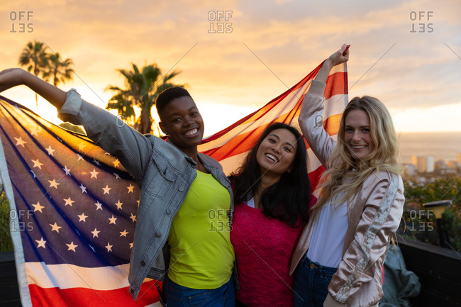 Portrait of a multi-ethnic group of friends hanging out on a roof terrace with a sunset sky, looking at camera and smiling, holding an American flag