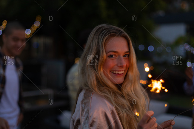 Portrait of a Caucasian woman hanging out on a roof terrace, looking at camera and smiling, holding a sparkler, with people in the background
