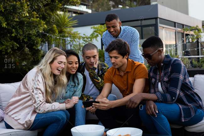 Front view of a multi-ethnic group of friends hanging out on a roof terrace, sitting on a sofa, using a smartphone and smiling