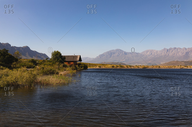 Breathtaking view of a lonely wooden cabin standing on the shore of a lake, near the mountains, on a sunny day