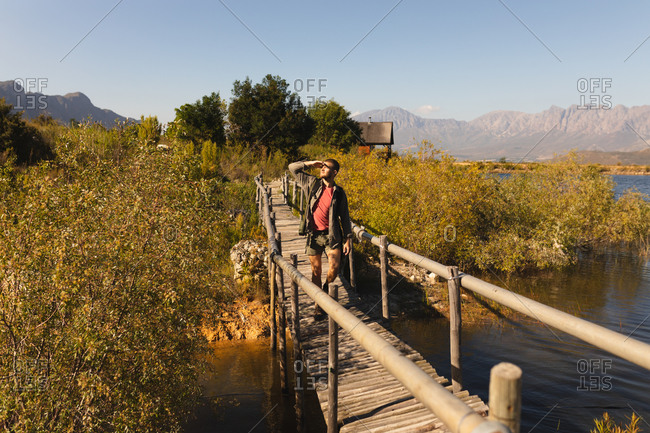 Front view of a Caucasian man having a good time on a trip to the mountains, standing on a bridge, enjoying his view, protecting his eyes from the sunshine, on a sunny day