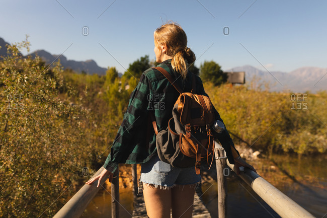 Rear view close up of a Caucasian woman having a good time on a trip to the mountains, standing on a bridge, enjoying her view, on a sunny day