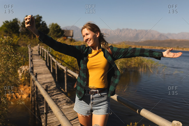 Front view low section of a Caucasian woman having a good time on a trip to the mountains, standing on a bridge, holding a smartphone and taking a selfie on a sunny day