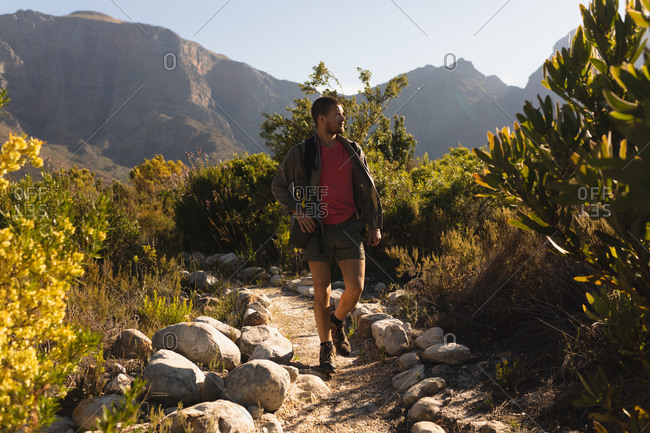 Front view of a Caucasian man having a good time on a trip to the mountains, walking on a dirt road on a field, on a sunny day