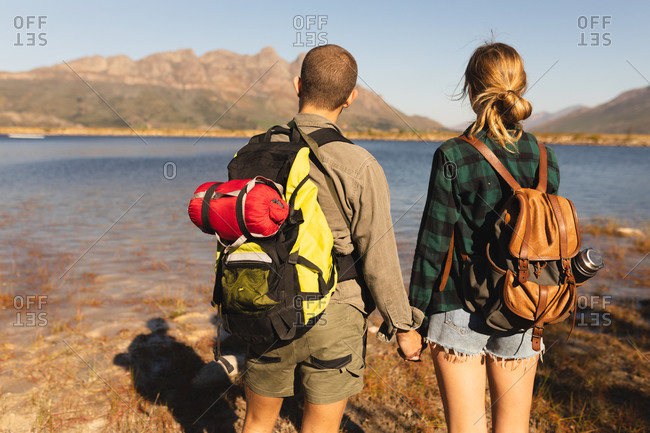 Rear view close up of a Caucasian couple having a good time on a trip to the mountains, standing on a shore, holding hands, on a sunny day