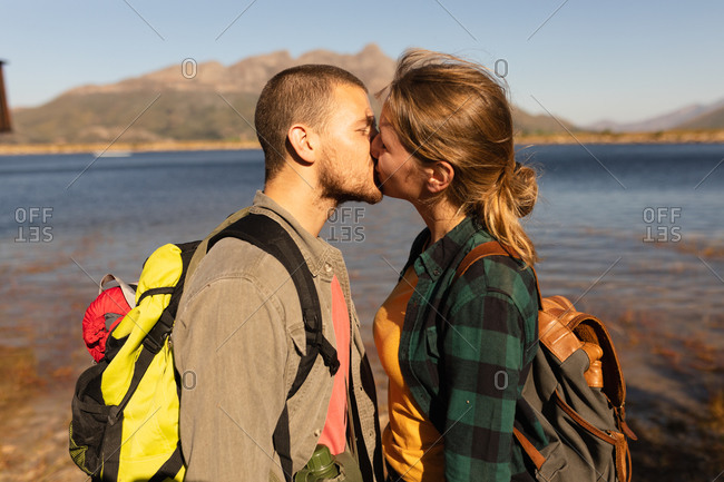 Side view close up of a Caucasian couple having a good time on a trip to the mountains, standing on a shore, kissing, on a sunny day