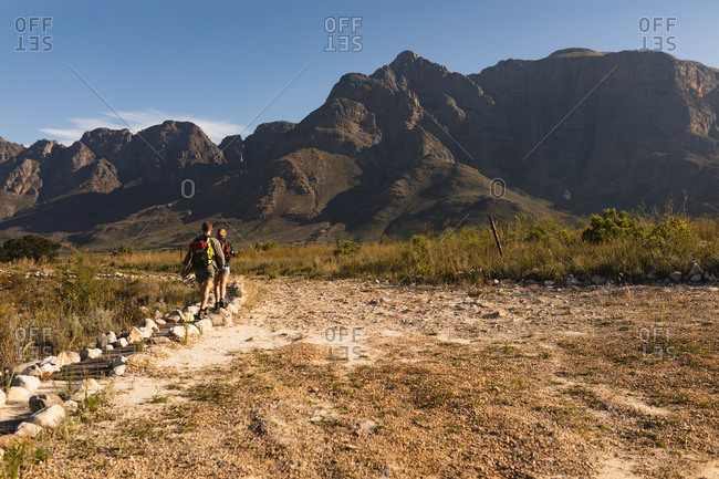 Rear view of a Caucasian couple having a good time on a trip to the mountains, walking on a path, on a sunny day
