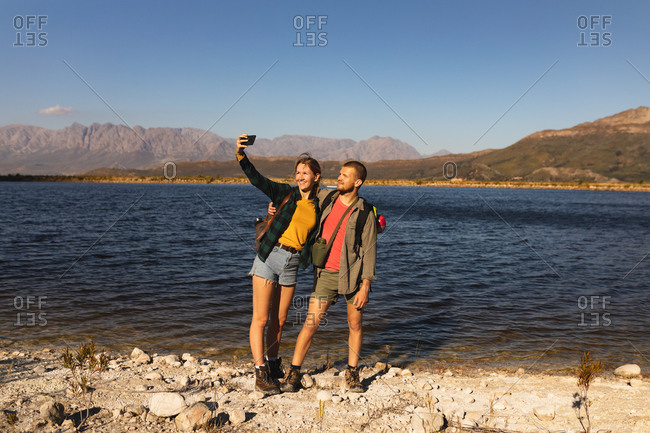 Front view close up of a Caucasian couple having a good time on a trip to the mountains, standing on a path, on a shore, taking a selfie, on a sunny day