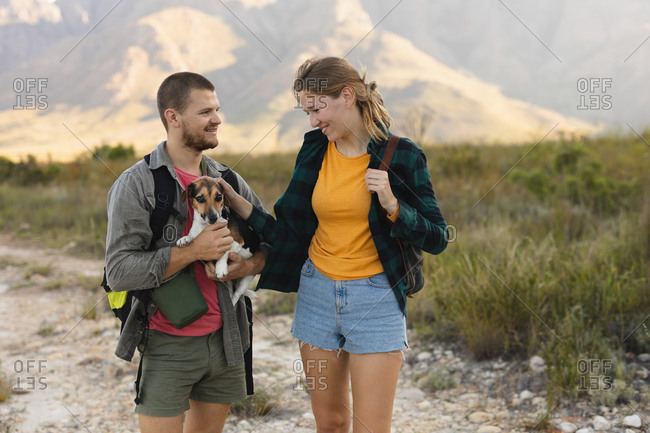 Front view close up of a Caucasian couple having a good time on a trip to the mountains, standing on a path, a man is holding a puppy, a woman is petting it, on a sunny day