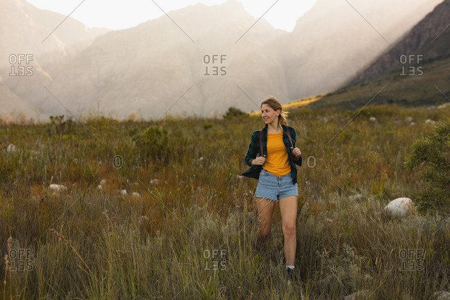 Front view of a Caucasian woman having a good time on a trip to the mountains, walking on a field, on a sunny day