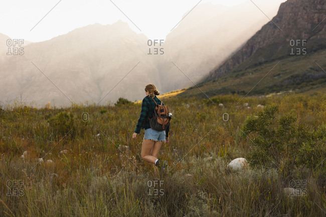 Rear view of a Caucasian woman having a good time on a trip to the mountains, walking on a field, on a sunny day