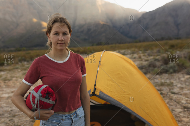 Portrait of a Caucasian woman having a good time on a trip to the mountains, looking at the camera, standing by a tent