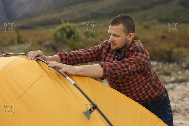 Side view of a Caucasian man having a good time on a trip to the mountains, putting up a tent