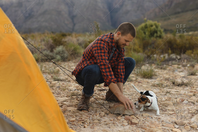 Side view of a Caucasian man having a good time on a trip to the mountains, putting up a tent, with a puppy laying by him