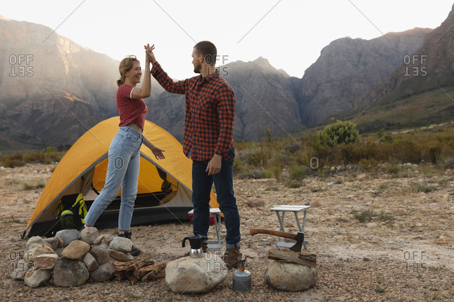 Side view of a Caucasian couple having a good time on a trip to the mountains, standing by a campfire, high fiving