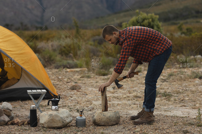 Side view of a Caucasian man having a good time on a trip to the mountains, holding an axe, preparing to chop a log