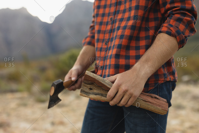 Side view mid section close up of a Caucasian man having a good time on a trip to the mountains, holding a log and an axe