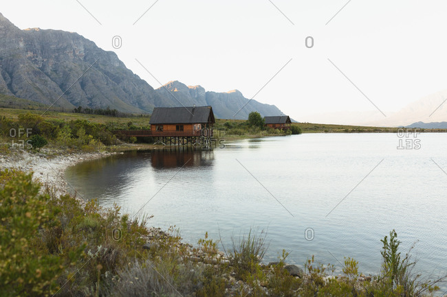 Breathtaking view of a lonely wooden cabin standing on the shore of a lake, near the mountains, on a cloudy day