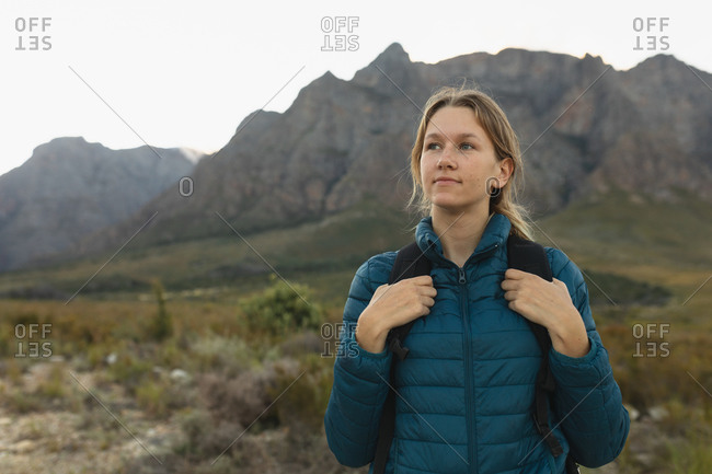 Portrait of a Caucasian woman having a good time on a trip to the mountains, wearing warm clothes, enjoying her view, smiling