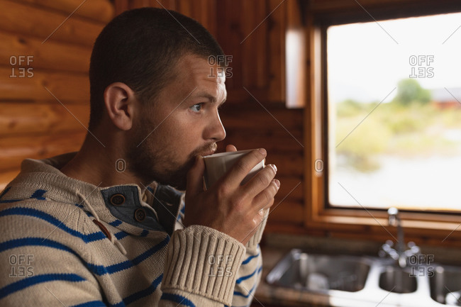 Side view close up of a Caucasian man having a good time on a trip to the mountains, sitting in a wooden cabin, drinking coffee
