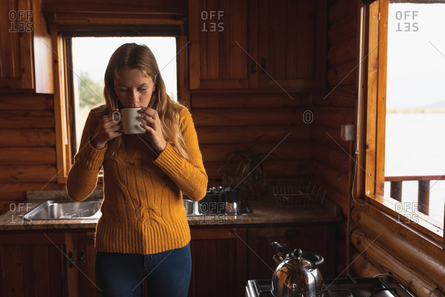 Front view of a Caucasian woman having a good time on a trip to the mountains, standing in a wooden cabin, drinking coffee