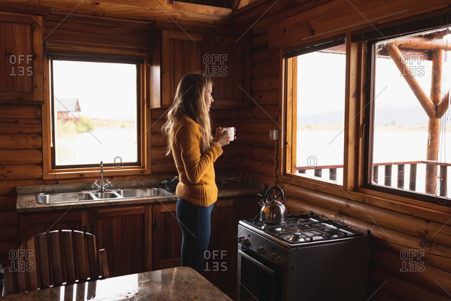 Front view of a Caucasian woman having a good time on a trip to the mountains, standing in a wooden cabin, drinking coffee, looking through the window