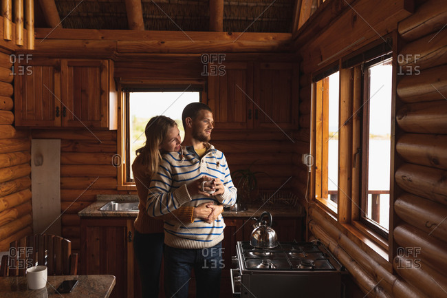 Front view of a Caucasian couple having a good time on a trip to the mountains, standing in a cabin, holding a cup of coffee, embracing, looking through  the widow