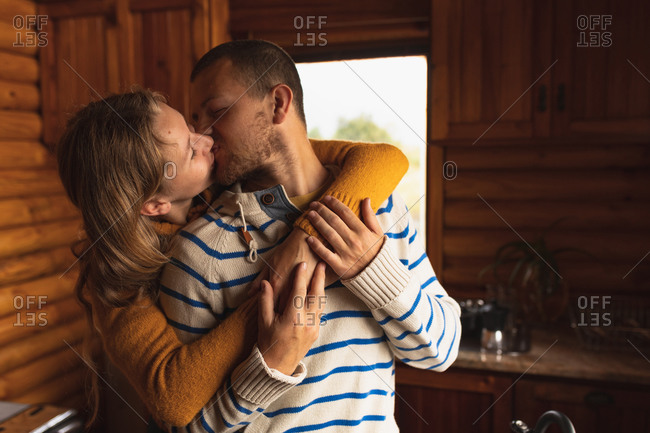 Front view of a Caucasian couple having a good time on a trip to the mountains, standing in a cabin, embracing and kissing