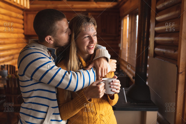 Front view close up of a Caucasian couple having a good time on a trip to the mountains, standing in a cabin, a woman is holding a cup of coffee and a man is kissing her, embracing, looking through  the widow