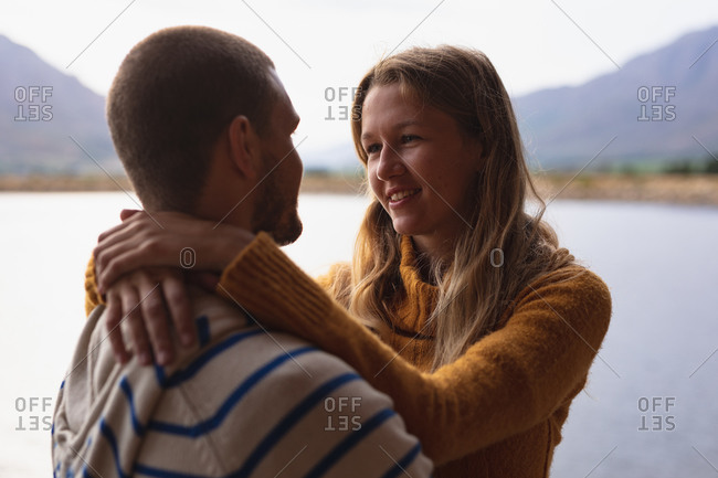 Side view of a Caucasian couple having a good time on a trip to the mountains, standing on a balcony in a cabin, embracing, looking at each other