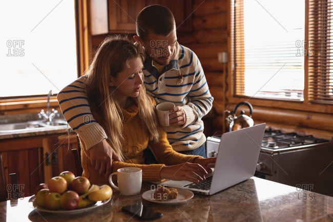 Side view of a Caucasian couple having a good time on a trip to the mountains, a woman is sitting and using laptop while a man is standing by her and embracing her