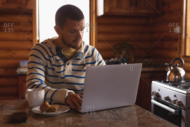Front view of a Caucasian man having a good time on a trip to the mountains, sitting by a table in a cabin, using laptop