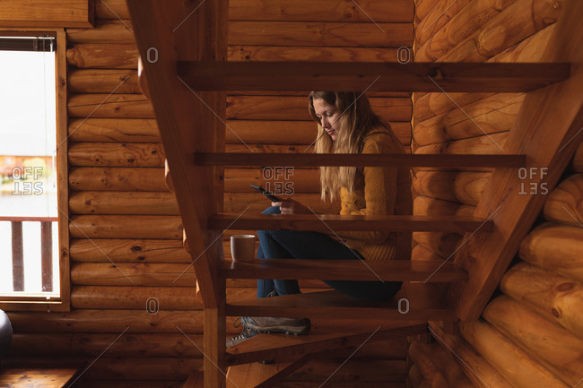 Side view of a Caucasian woman having a good time on a trip to the mountains, sitting on the stairs in a cabin, using smartphone