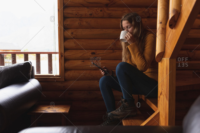 Side view close up of a Caucasian woman having a good time on a trip to the mountains, sitting on the stairs in a cabin, using smartphone, drinking coffee