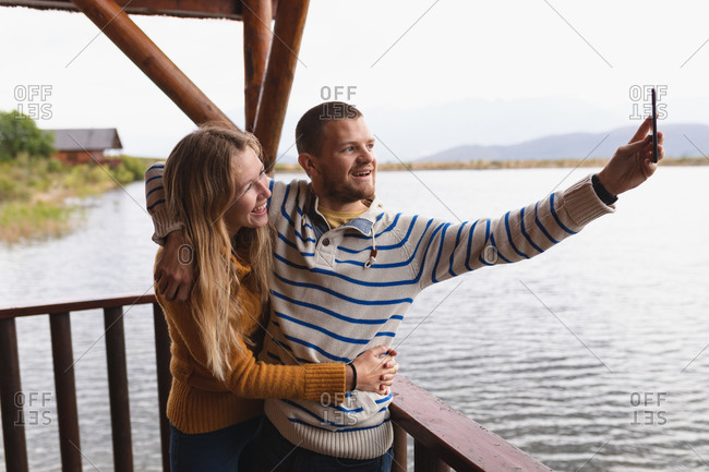 Side view of a Caucasian couple having a good time on a trip to the mountains, standing on a balcony in a cabin, embracing, taking a selfie