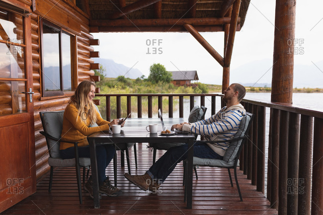 Side view of a Caucasian couple having a good time on a trip to the mountains, sitting by a table on a balcony in a cabin, a woman is using her smartphone, and a man is using his laptop
