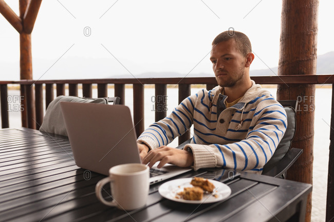 Side view of a Caucasian man having a good time on a trip to the mountains, sitting by a table on a balcony in a cabin, using laptop