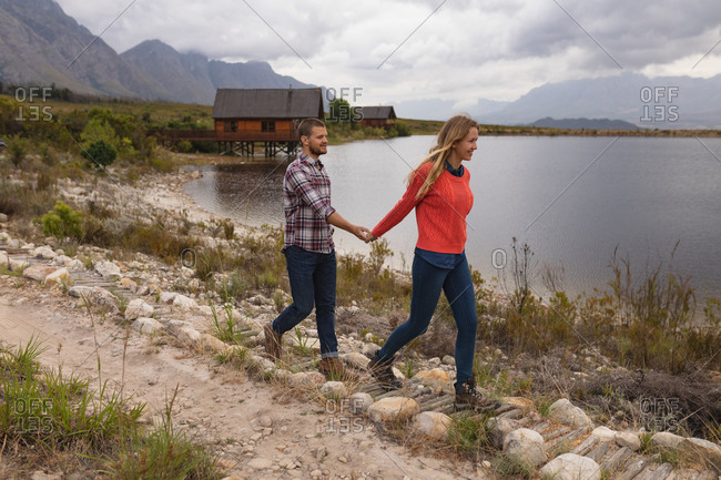 Side view of a Caucasian couple having a good time on a trip to the mountains, walking on a path on a lake shore, holding hands