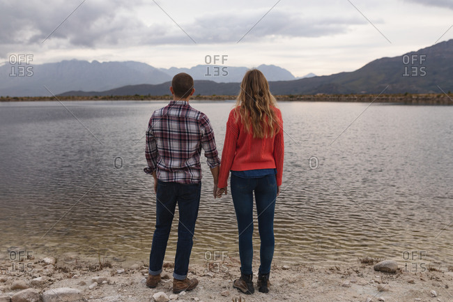 Rear view close up of a Caucasian couple having a good time on a trip to the mountains, standing on a lake shore, holding hands