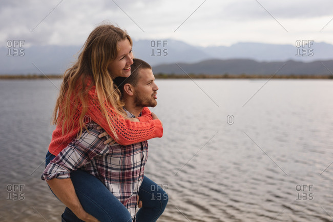 Side view close up of a Caucasian couple having a good time on a trip to the mountains, standing on a lake shore, a man is carrying a woman piggy back