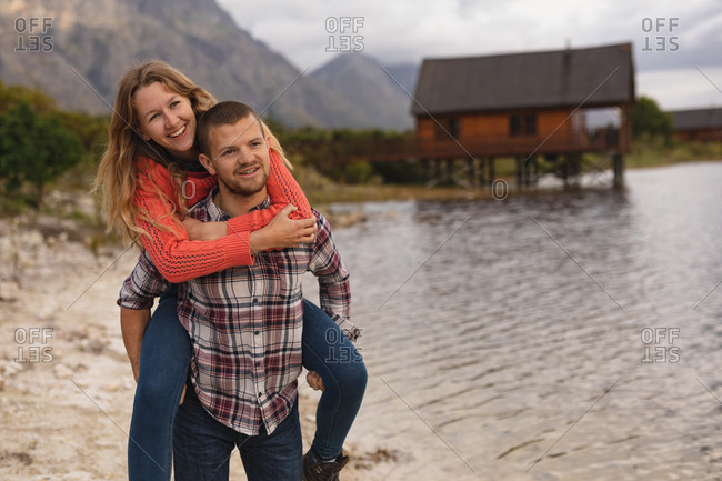 Front view close up of a Caucasian couple having a good time on a trip to the mountains, standing on a lake shore, a man is carrying a woman piggy back