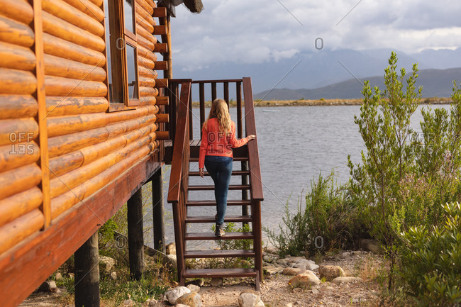 Rear view of a Caucasian woman having a good trip to the mountains, walking on a stairs to a cabin